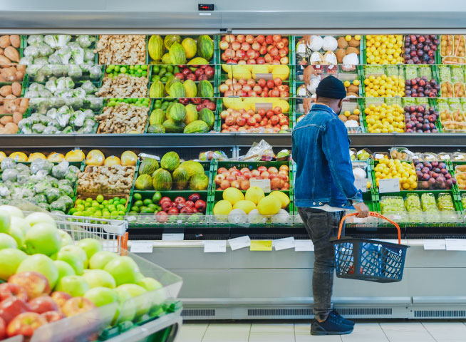 Man shopping in the produce section of a grocery store