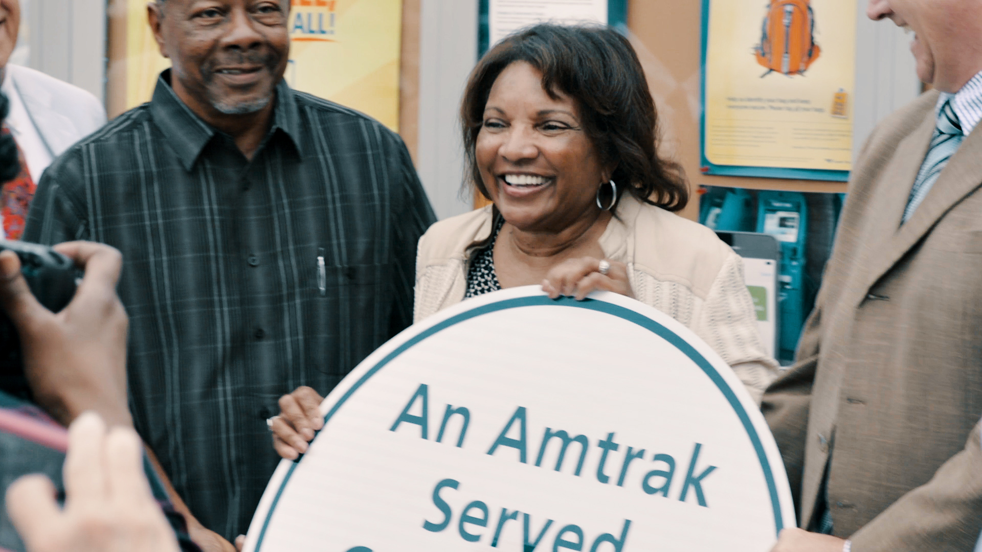 Photo of woman holding Amtrak sign
