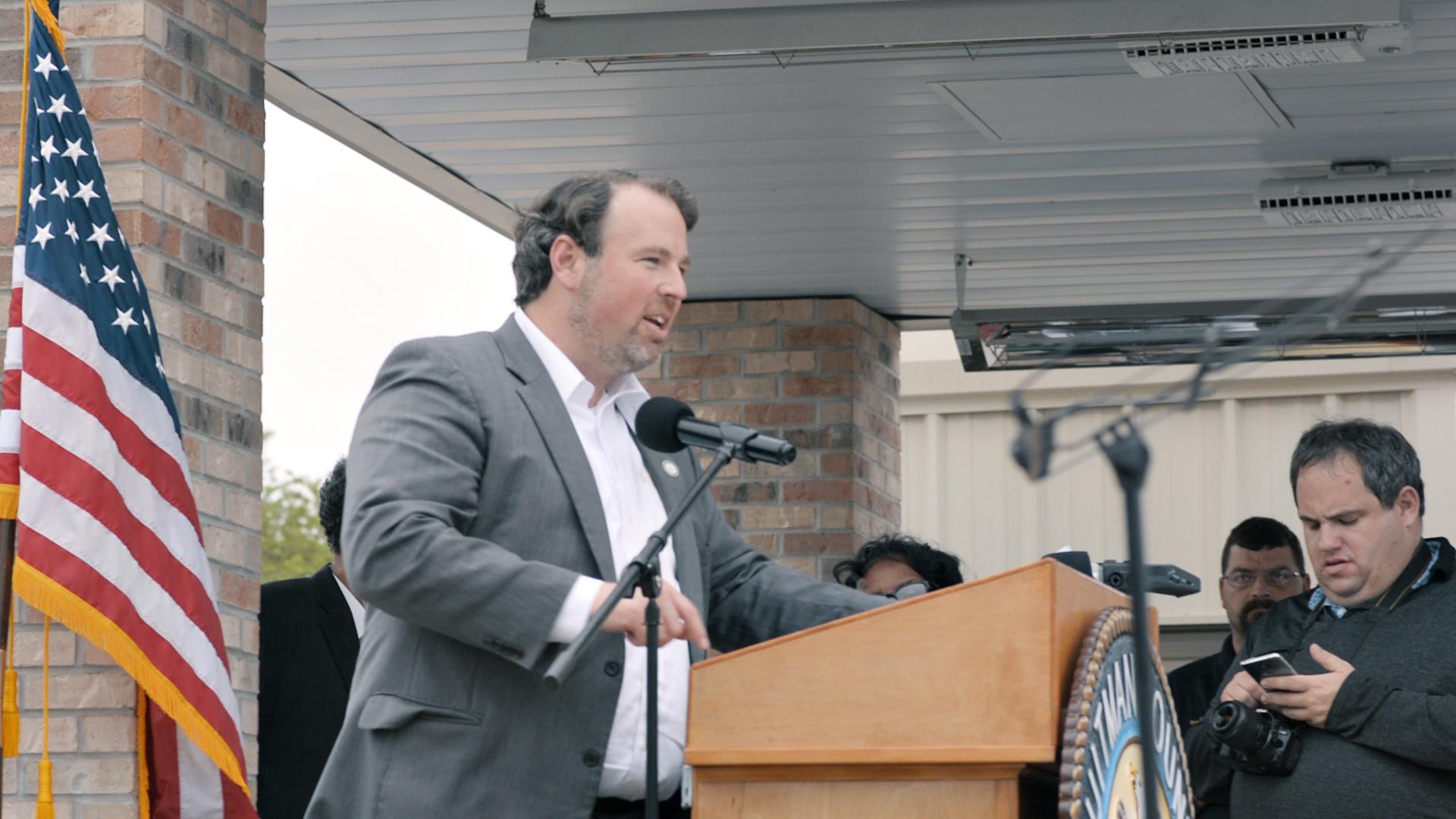 Photo of man at podium, speaking