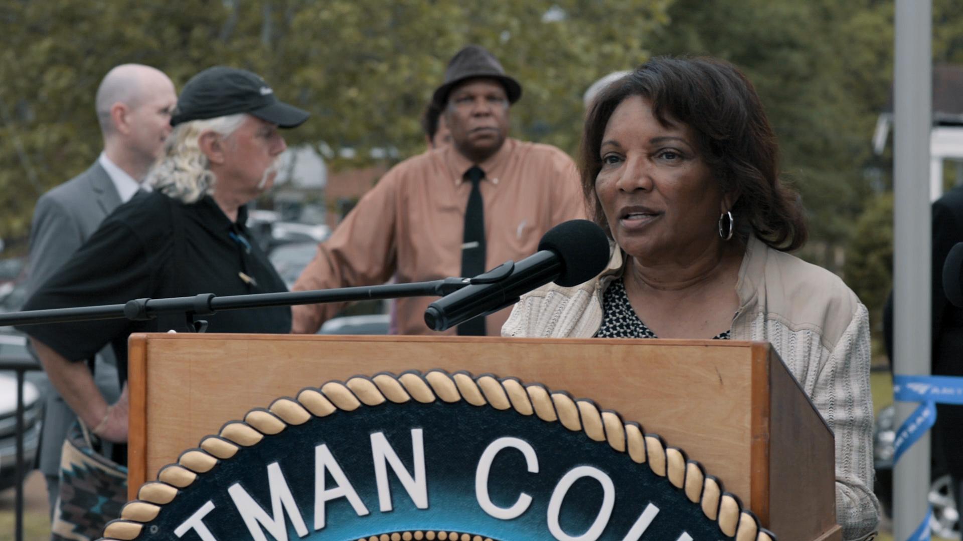 Photo of woman at podium, speaking